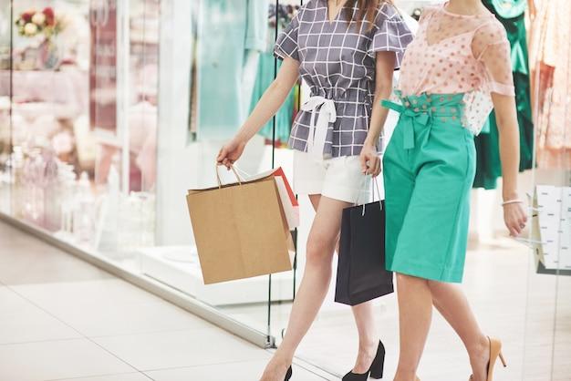 ショッピングに最適な日。衣料品店を歩きながら笑顔でお互いを見つめるバッグを持つ2人の美しい女性