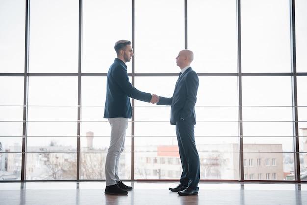 オフィスでの会議中に握手する2つの自信を持ってビジネスの男性