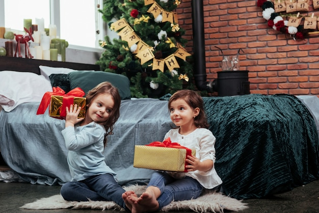 それぞれに良いプレゼントがあります。ベッドの近くのすてきな部屋に屋内で座っているこれらの2人の子供への贈り物でクリスマス休暇