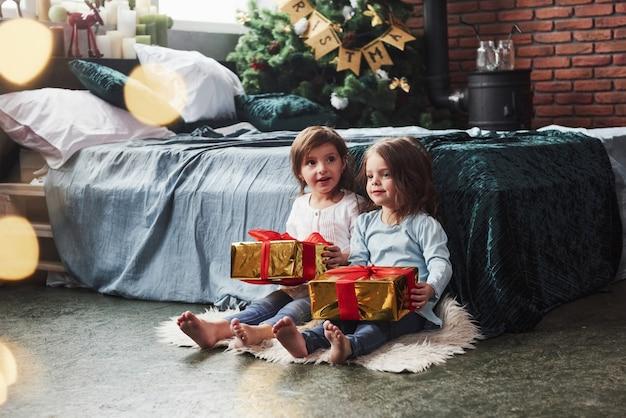 今日、誰かがプレゼントをもらっています。ベッドの近くのすてきな部屋に屋内で座っているこれらの2人の子供への贈り物でクリスマス休暇