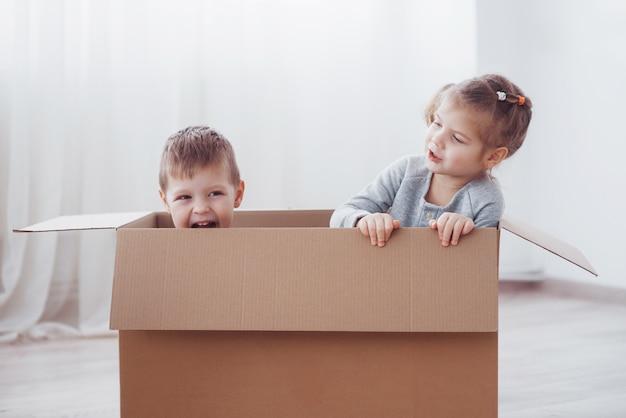 2人の小さな子供の男の子と女の子が新しい家に引っ越しました。コンセプト写真..子供たちは楽しい時を過します。