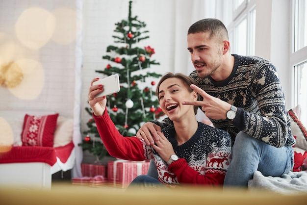 セルフィーを取る。 2本の指のジェスチャーを示す男。幸せな若者は、クリスマスの装飾が付いている部屋の窓辺に座っています。