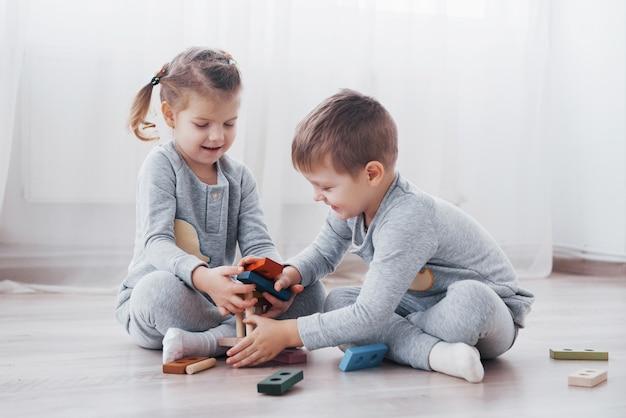 子供たちは子供部屋の床でおもちゃデザイナーと遊ぶ。カラフルなブロックで遊ぶ2人の子供。幼稚園の教育ゲーム
