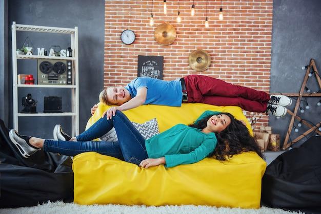 2つの美しい人々、男性と女性の家の中の黄色のソファの上に横たわる