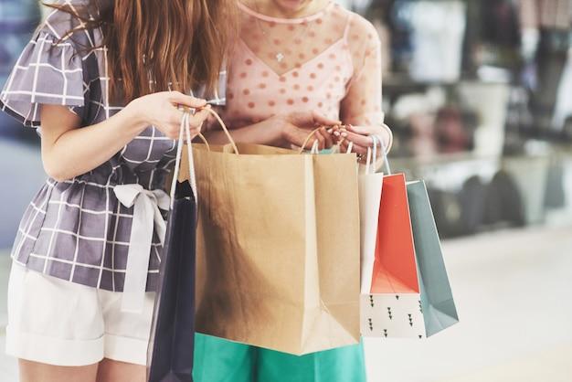 ショッピングに最適な日。衣料品店で歩きながら笑顔でお互いを見ている買い物袋を持つ2つの美しい女性
