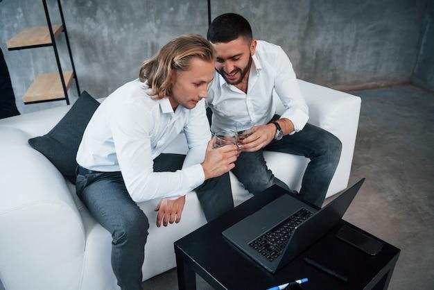 気分が良い2人の同僚が仕事の成功を祝い、ウイスキーを飲みながらソファに座って