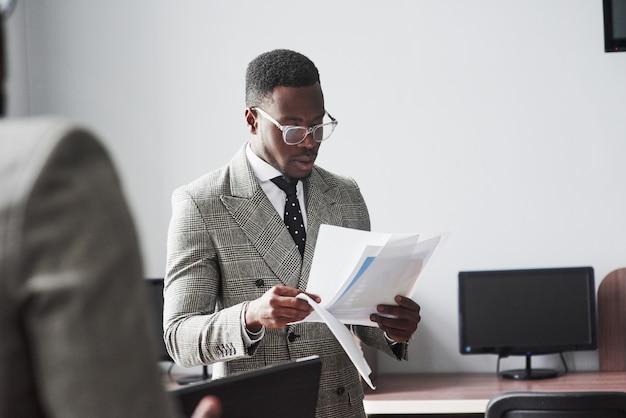 オフィスでの会議で交流する2人の若いアフリカ系アメリカ人ビジネスマンの画像