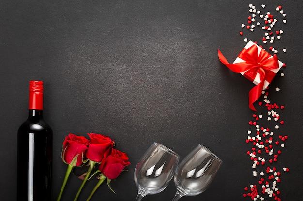 ワインのボトル、2つのグラス、暗い背景に赤の弓とギフトボックスの組成物。バレンタインの日、日付、愛。