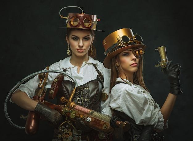 腕を持つスチームパンクのスタイルに身を包んだ2人の女性