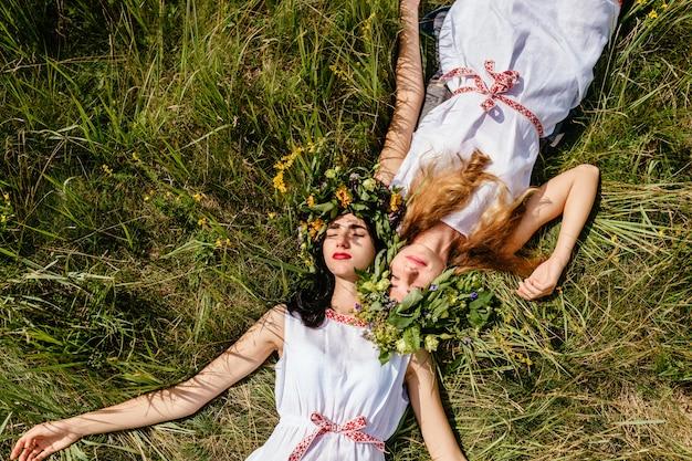 夏には草の上に横たわると生活を楽しんでいる美しい若い女の子の友人のカップル。スラブの伝統的な衣装を着た2人の愛する女性の肖像画。自然で過ごす友人。
