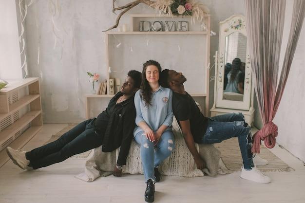 多文化の愛と関係の概念。若い白人女性は、アフリカの2人の暗い肌の男性の間に座っています。人種を受け入れるカップルのソフトフォーカススタジオポートレート。異人種間の友情。