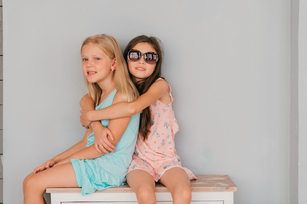 壁に灰色の壁に対してドレッサーでハグする2つの美しいスタイリッシュな女の子。