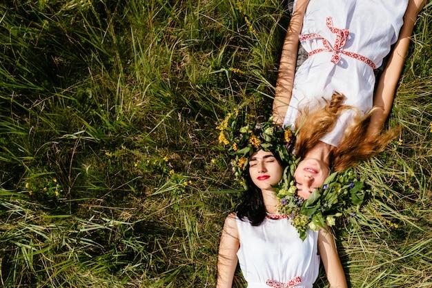 夏に草の上に横たわると生活を楽しんでいる美しい若い女の子の友人のカップル。スラブの伝統的な衣装を着た2人の愛する女性の肖像画。