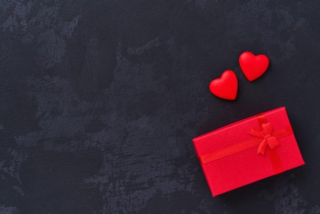 ギフトボックスと黒の背景、上面に2つの赤いハート。