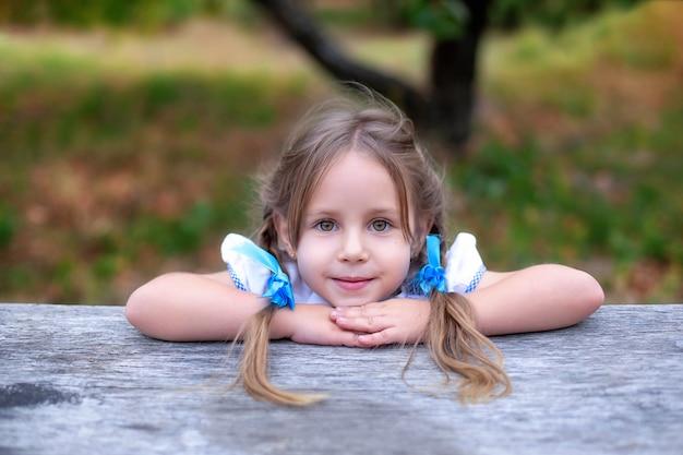 彼女の頭に2つのおさげ髪のかわいい女の子は、顔の近くの手を折る。夏の庭で大きな目で子供の女の子を笑っています。