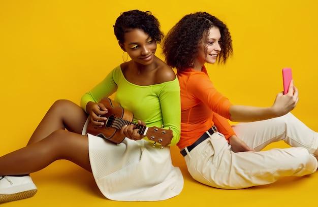 小さなギターでカラフルな夏服の2人の若い美しい女性