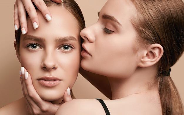 明確な新鮮な若い顔の皮膚を持つ2つの美しい官能的な若い女の子