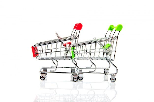 白で隔離される2つの空の赤と緑のショッピングカート