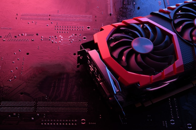 コンピューターゲームのグラフィックカード、回路基板、マザーボードに2つのクーラーが付いたビデオカード。閉じる。赤青照明あり