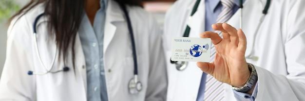 プラスチックカードを示す2人の医者