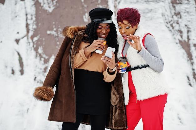 2 женщины афроамериканца в овчине и меховой шыбе представили на зимний день с чашками кофе и смотреть мобильный телефон.