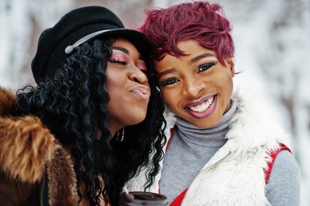 冬の日にポーズをとって羊皮と毛皮のコートで2人のアフリカ系アメリカ人女性の顔を閉じる