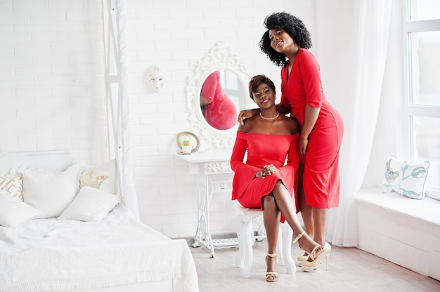 赤い美容ドレス、白いビンテージルームでイブニングドレスをポーズセクシーな梨花の2つのファッションアフリカ系アメリカ人モデル。