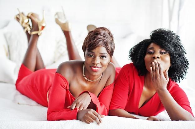 赤い美しさのドレスと黄金のハイヒールの2つのファッションアフリカ系アメリカ人モデル、イブニングドレスをポーズセクシーな梨花はベッドにあります。