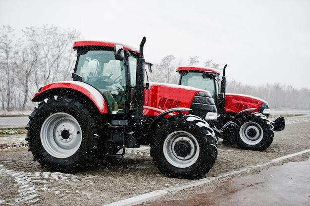 2つの新しい赤いトラクターが雪の天気で滞在します。