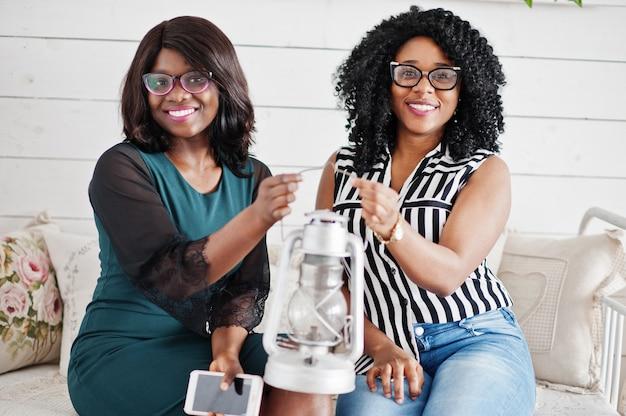 2つのアフリカの女性の友人は、ソファの屋内白い部屋に座っている眼鏡を着用します。彼らは古いランタンを一緒に持っています。