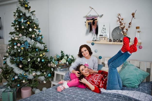 2人のガールフレンドは、クリスマスの飾りが付いている部屋のベッドで楽しんで冬のセーターを着ています。