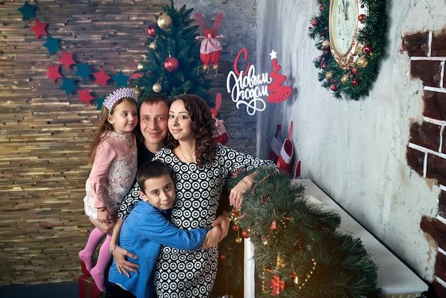 暖炉のそばの木で幸せな家族。ママ、パパ、冬休みの2人の子供。クリスマスイブと大晦日。