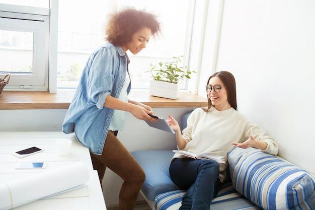 2人の女の子が一緒に勉強しています。青いシャツを着た少女は、白いセーターの少女にタブレットを見せています。最後のものはノートを持っています。女の子は笑っています。
