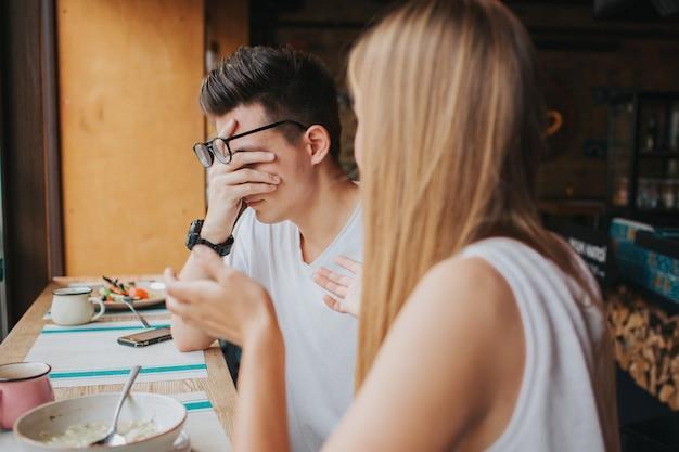 コーヒーハウス、バー、またはレストランでの2人の若者の口論