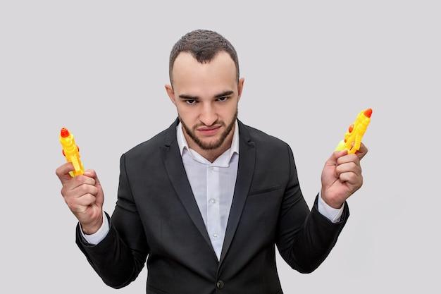 スーツで遊び心のある若い男が立ち、カメラを見てください。彼はポーズします。男は2つの黄色い水鉄砲を保持しています。彼は怒っています。