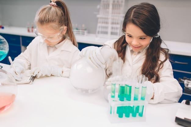 学校の実験室で化学を学ぶ白衣の2人の小さな子供。実験室や化学キャビネットで実験を行う保護メガネの若い科学者。実験の材料を勉強します。