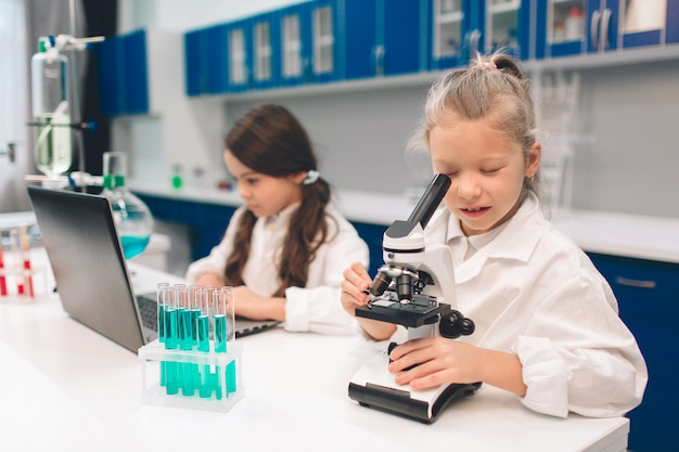 2 маленького ребенка в пальто лаборатории изучая химию в лаборатории школы. молодые ученые в защитных очках делают эксперимент в лаборатории или химическом кабинете. работа на пк