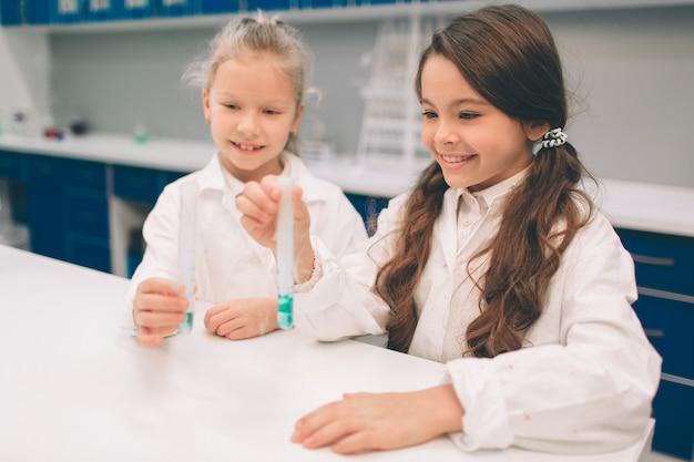2 маленького ребенка в пальто лаборатории изучая химию в лаборатории школы. молодые ученые в защитных очках делают эксперимент в лаборатории или химическом кабинете. изучение ингредиентов для экспериментов.