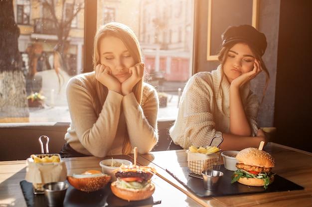 2人の退屈した若い女性がテーブルに座って、食べ物を見ています。彼らはあごの下に手を保ちます。モデルはカフェにいます。外は太陽が輝いています。