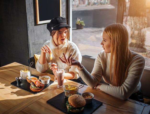 テーブルで2人の友人が一緒に座っています。キャップの若い女性は別のと主張します。彼女は怒っています。ブロンドの女の子は彼女の友人を見て、彼女に話します。