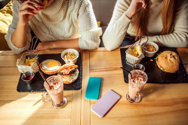 食べ物や飲み物でいっぱいのテーブルのビューをカットします。テーブルに座っている若い女性がいます。 2台の電話が横になっています。食べるモデル。