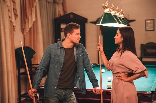 若い男と女はビリヤードルームに立ち、お互いを見てください。彼らはライバルです。人々は2つのビリヤードキューを手に持っています。