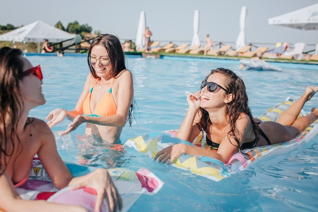 フロートで泳いでいるプールの水に立っているビキニのモデル。中間の手で水しぶきの女性。他の2つのモデルは日焼けを楽しんでいます。彼らは微笑む。