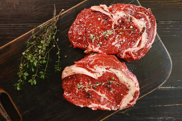 オリーブオイルとスパイスで揚げる準備ができている2つの生の霜降り牛ステーキ。
