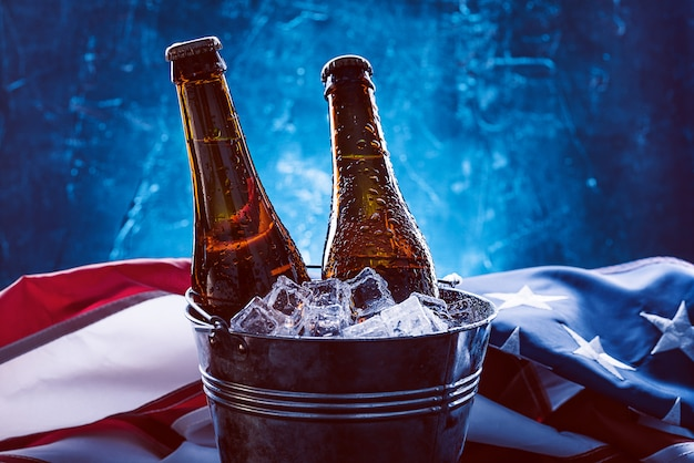 アメリカの国旗が近くにある氷のバケツにビール2本。独立記念日のお祝いのコンセプト