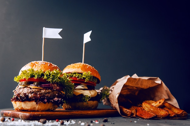 牛肉を切るために使用される2つのおいしそうな、おいしい自家製バーガー。木製のテーブルの上。