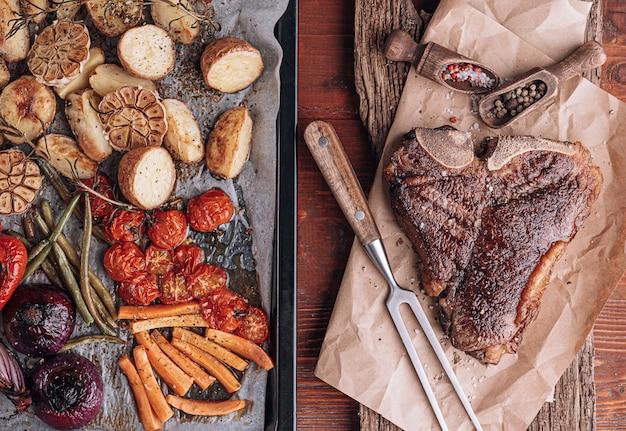 焼きたての野菜で焼いたジューシーで新鮮な農家の霜降りビーフステーキの2つの素晴らしいディナーのコンセプト