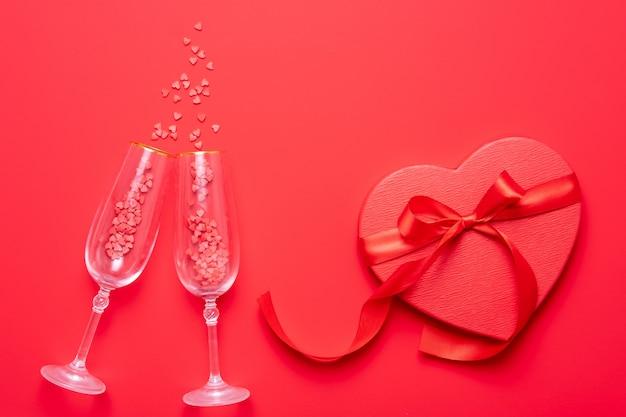 赤いハートのスプラッシュと2つのシャンパングラス形赤の背景に紙吹雪。トップビュー、フラットレイアウト、コピースペース。バレンタインデーのコンセプト