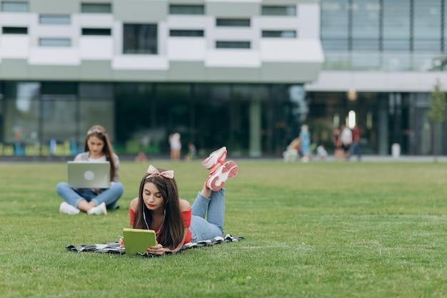フリーランスで働きます。学生の学習。緑の芝生に座っている2人のかわいい女の子の友人。