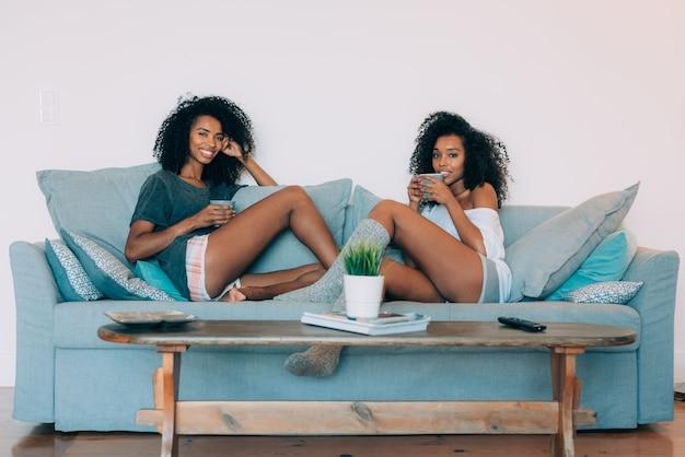 コーヒーを飲みながらソファに座って幸せな若い2人の黒人女性